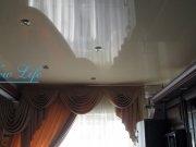 Лаковый (глянцевый) белый натяжной потолок с потолочными светильниками в гостиной
