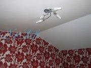Белый матовый натяжной потолок с люстрой потолочного крепления на мансарде