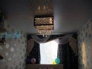 Матовый белый натяжной потолок с горящей потолочной люстрой в спальне