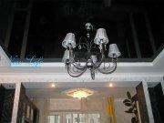 Многоуровневый натяжной потолок из гипрока и черного лакового полотна с люстрой на крючке