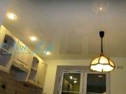 Лаковый (глянцевый) натяжной потолок со встроенными светильниками и люстрой на кухне