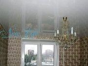 Лаковый (глянцевый) натяжной потолок белого цвета с люстрой на крючке в команте