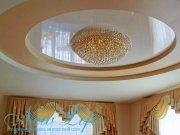 Многоуровневый натяжной потолок  с лаковой фактурой по центру в форме круга