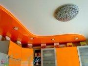 Сочетание глянцевой оранжевой и светлой матовой фактуры натяжного потолка в двухуровневой конструкции