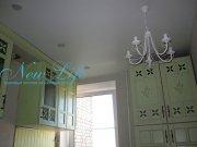 Сатиновый белый натяжной потолок с люстрой и потолочными светильниками на кухне
